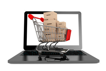 Online shopping concept. Shopping Cart with Boxes over Laptop