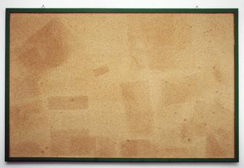 Benutzte Kork-Pinnwand mit Abdrücken von Zetteln und Fotos