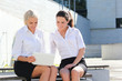 two attractive business women sitting with laptop over street ba