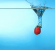 Strawberry splashing into water on blue background