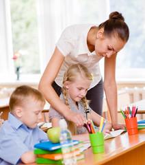 Teacher helps the schoolkids with schoolwork in classroom
