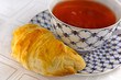 closeup of pile croissants & cup of tea