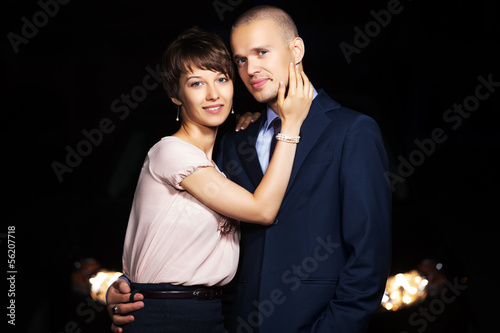 Young couple in the night in front of car headlights