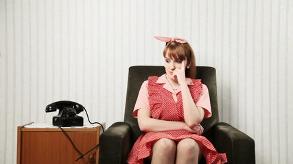 Housewife sitting on the chair is waiting for a phone call