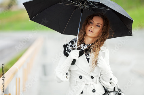 Beautiful woman with umbrella in the rain