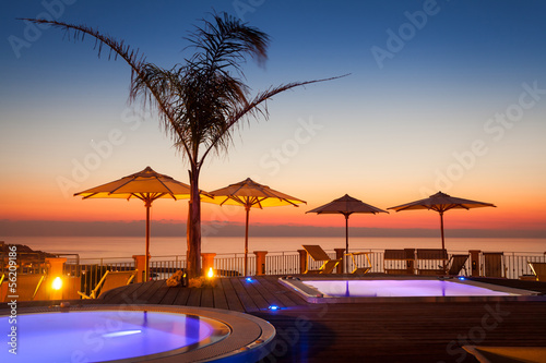 Summer time: beautiful view of red dawn at pool area with palm a