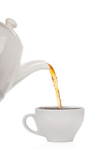 Pouring tea into a cup isolated on white background
