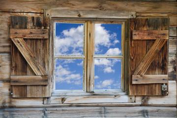 Fenster einer Berghütte mit Himmel in Südtirol