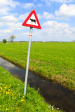 Cow warning sign in a dutch landscape