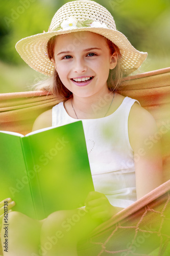 Girl with book resting on a hammock in the garden