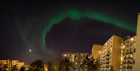 Green aurora borealis over city buildings