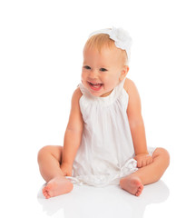 happy little baby girl in white dress laughs isolated on white