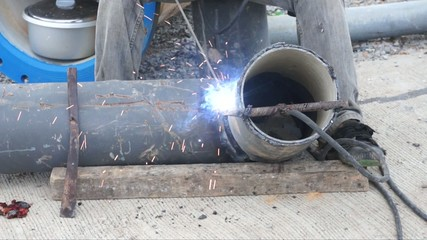 Welder uses torch for welding pipe metal on site.