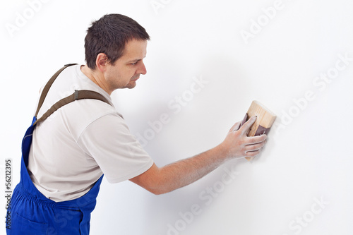 Worker scrubbing the wall with sandpaper