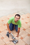 Man laying floor tiles - with copy space