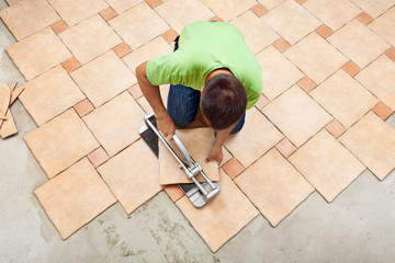 Man laying ceramic floor tiles