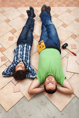 Father and son resting while laying floor tiling