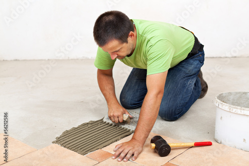 Man laying floor tiles - spreading the adhesive