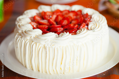 Fototapeta Delicious strawberry cake with strawberries and whipped cream