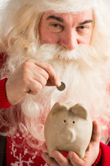 Authentic Santa Claus holding piggy bank and putting golden coin