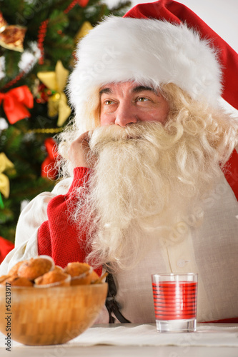 Portrait of happy Santa Claus at home eating cookies and drinkin