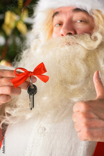 Santa Claus holding keys of new house or apartment and thumbs up