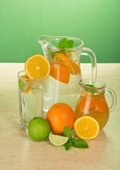 Jugs with drinks, a glass, a juicy lime and oranges