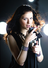 Young woman singing with microphone with back light and flying h