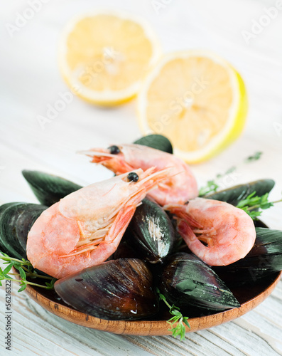 Mussels in the shell and shrimp with lemon on wooden background