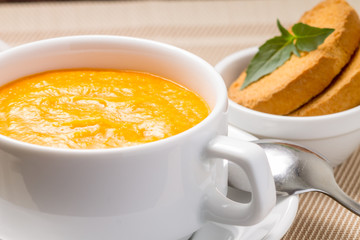 Pumpkin soup in white bowl with fresh basil