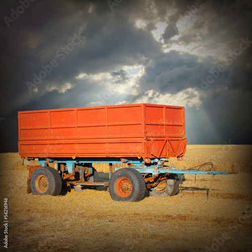 A empty tractor trailer on a wheat field.