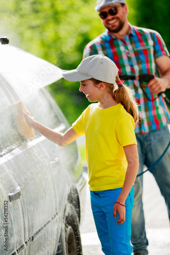 Carwash - young girl helping father to wash car