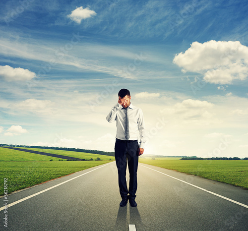 man standing on the road and looking down