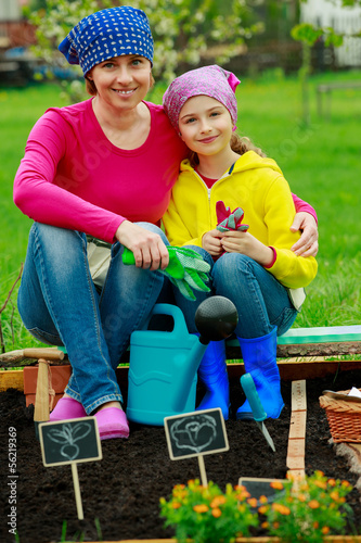 Gardening - girl helping mother in the garden