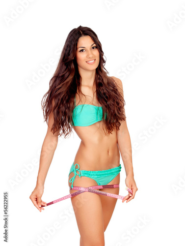 Slim brunette girl with tape measure in bikini