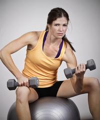 Strong Beautiful Woman Lifting free weights