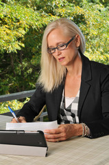 Business woman signing documents outdoors