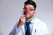 young doctor with clown red nose listens to himself