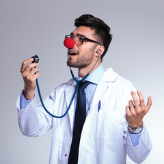 young doctor with red nose singing in the stethoscope