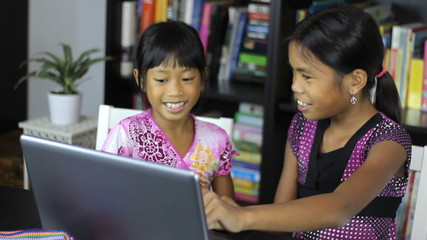 Two Asian Sisters Laugh While Using A Laptop Computer