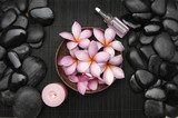 frangipani flower in bowl with candle and oil and pile stones