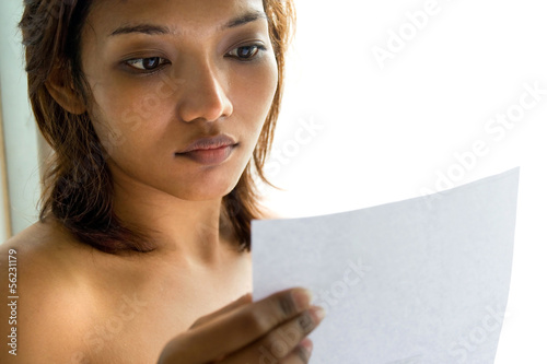 Young woman reading a letter.