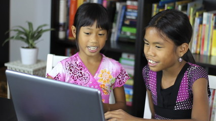 Two Asian Sisters Working On A Laptop Computer
