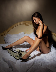 Beautiful girl in black lingerie in bed with a typewriter.