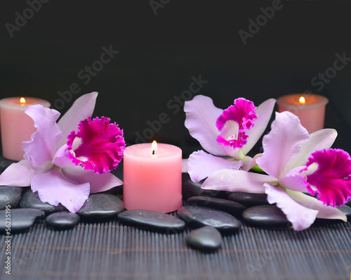 Spa setting-beautiful orchid with candle and zen stones on mat