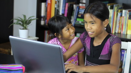 Young Asian Sisters Having Fun On Their Computer