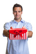 Smiling latin man hands over the christmas present