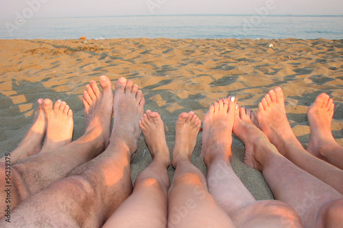 barefoot of a family on the shore of the sea on the beach with c