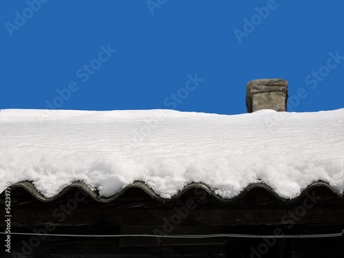 snow on a roof of the old house