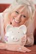 Glückliche Seniorin mit Sparschwein